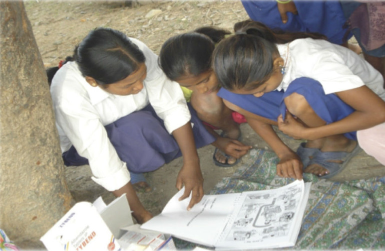 """Young girls in Nepal study the booklets based on """"Our Bodies, Ourselves."""""""
