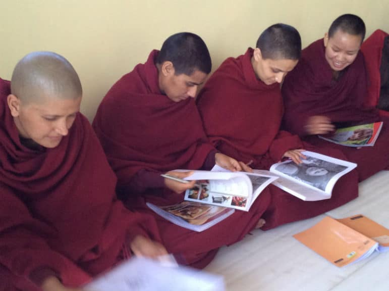 """Buddhist monks in India reading """"Healthy Body, Healthy Mind"""""""