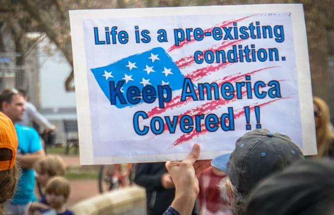 """Sign saying """"Life is a pre-existing condition. Keep America Covered!"""