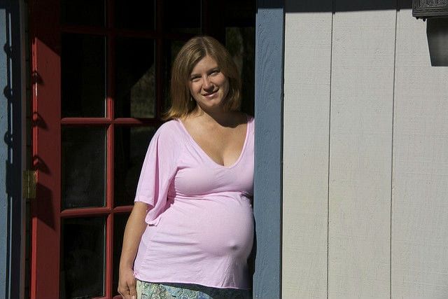 Pregnant woman leaning against doorframe in white shirt