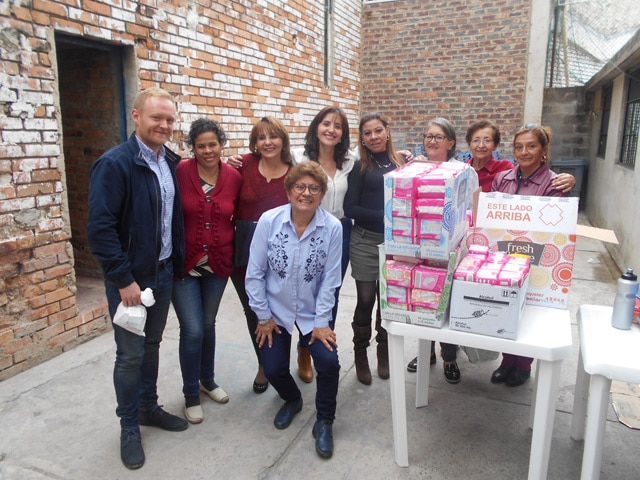 A group of people outside a prison delivering menstrual supplies