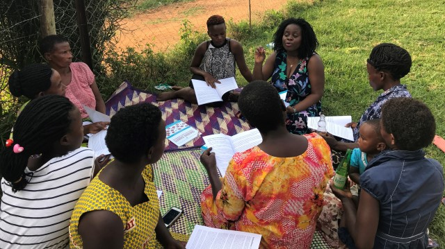 """A group of women in Uganda sit outdoors in a circle and discuss the Luganda edition of """"Our Bodies, Ourselves"""""""